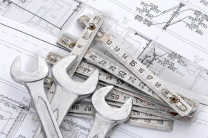 Spanners over house plan for construction or reconstruction